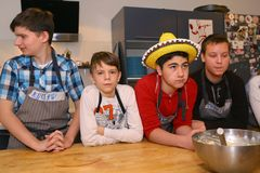 Teenager kids team cooking having fun. Moscow, Russia, November 21, 2017: Unidentified teenager kids cooking pasta on culinary master class - happy event Stock Image