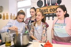 Teenager kids team cooking having fun. Moscow, Russia, November 21, 2017: Unidentified teenager kids cooking pasta on culinary master class - happy event Royalty Free Stock Images