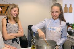 Teenager kids team cooking having fun. Moscow, Russia, November 21, 2017: Unidentified teenager kids cooking pasta on culinary master class - happy event Stock Photos