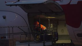Airport worker unloading aircraft at night