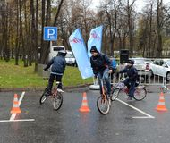 Boys on bicycles go around obstacles at a sporting event. MOSCOW, RUSSIA - OCTOBER 19, 2013:Boys on bicycles go around obstacles at a sporting event Royalty Free Stock Photography
