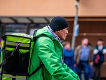 Moscow, Russia - October 19, 2019: Courier of Asian ethnicity in uniform and branded green delivery club backpacks with bike on