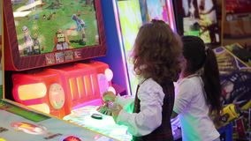 Little girls playing video arcade game in game center. Moscow, Russia - October, 2015: little girls playing video arcade game in game center stock video footage