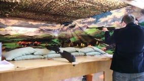 Man playing video arcade shooting rifle range game. Moscow, Russia - October, 2015: Man playing video arcade shooting rifle range game stock video footage