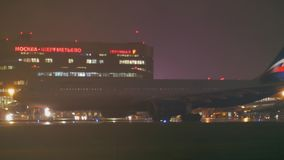 Aeroflot plane leaving Terminal F of Sheremetyevo Airport at night, Moscow. MOSCOW, RUSSIA - OCTOBER 04, 2017: Night view of Aeroflot airplane with headlight stock video