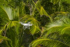 MOSCOW, RUSSIA - 2 October, 2017: a Phantom 4 Pro drone in flight, green trees in the background, selective focus on the drone. stock photography