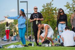 Group of young people having fun in the park at day time. Moscow, Russia - September 9, 2017: Group of young people having fun in the park at day time Royalty Free Stock Image