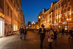 People and architecture at Arbat walking street in Russia. Moscow, Russia - September 21, 2017: People and historical building decorated by warm light at Arbat Royalty Free Stock Photos