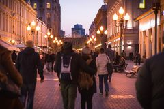 Sweet twilight scene of Arbat street. Moscow, Russia - September 21, 2017: People and historical building decorated by warm light at Arbat walking street during Royalty Free Stock Photography
