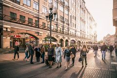 Walking people at Arbat street. Moscow, Russia - September 21, 2017: People walking around crowded Arbat street with scene of sunlight behind historic building Stock Image