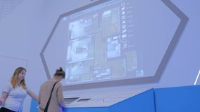 Woman using interactive touchscreen console. MOSCOW, RUSSIA - SEPTEMBER 10, 2017: Smart City Exhibition. Woman using interactive touchscreen console in front of stock video footage