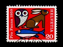 Fish, Owl, and hare, Fauna serie, circa 1959. MOSCOW, RUSSIA - SEPTEMBER 3, 2017: A stamp printed in Switzerland shows Fish, Owl, and hare, Fauna serie, circa Royalty Free Stock Photography