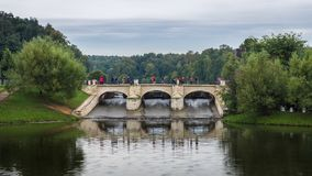 Brick bridge with tourists surrounded by green tree Royalty Free Stock Photos