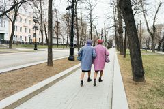 Moscow, Russia - 04 20 2019: Two elegant older grandmothers identically dressed royalty free stock image