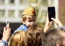 Victory Day in Moscow.a boy in a military pilot`s cap sits on his father`s shoulders. 2018.09.05, Moscow, Russia. Victory Day in Moscow.a boy in a military stock photography