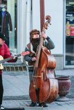 A young man playing contrabass at the central touristic street. Street entertainment at winter time. royalty free stock image