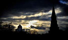 Moscow& x27; s Cristo la torre de la catedral y del Kremlin del salvador silueteada en puesta del sol imagenes de archivo