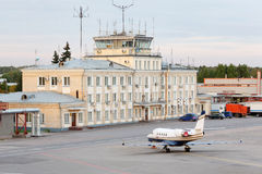 Small airliner stands near building Stock Image