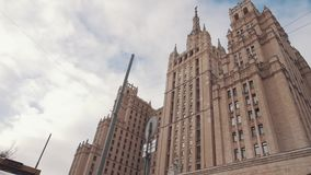 Moscow State University building agains white clouds blue sky, dry trees stock video