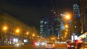 Moscow street traffic and 'Moscow city' business district skyscrapers at night. Clip stock video footage