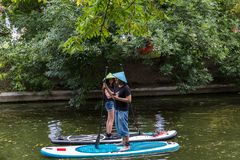 Moscow, summer Park-July 05, 2018: Young girl and man in straw hats standing on surfboards stock photo