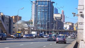 Moscow urban highway traffic on sunny spring day 4K shot. Urban highway traffic on sunny day 4K pan shot, wide lens version clip stock video footage