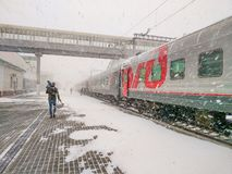The Moscow-Vladivostok train is at the station. A man with a child is landing stock image
