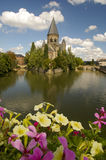 Moselle river in metz flower in focus. Moselle river and petunia flowers church and bridge in background in the town of metz france Royalty Free Stock Images
