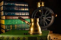 Mosiężny turek z fasolami obok i kawowym ostrzarzem na tle Atmosfera stara biblioteka z starymi książkami wokoło na ciemnym tle fotografia stock