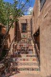 Mosiac kroki prowadzi do drugi opowieści wejścia i zamkniętej żelaznej bramy w adobe budynku zdjęcie royalty free