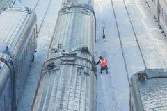 MOSKAU, FEB 01, 2018: Wintertagesansicht über Bahnwartungsarbeiter in der orange Warnweste, die Personenzüge Ca kontrolliert Stockbild