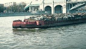 MOSKAU, RUSSLAND - APRIL, 29, 2017 Gedrückter Lastkahn voll des industriellen Abfalls, der auf den Fluss transportiert wird Moder Stockfotografie