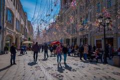 MOSKAU, RUSSLAND APRIL, 24, 2018: Leute in den festlichen Weihnachtslichtern auf Nikolskaya-Straße mit vielen Souvenirladen herei Stockfotos