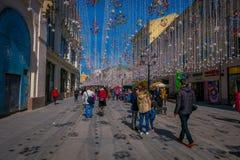 MOSKAU, RUSSLAND APRIL, 24, 2018: Leute in den festlichen Weihnachtslichtern auf Nikolskaya-Straße mit vielen Souvenirladen herei Lizenzfreie Stockbilder