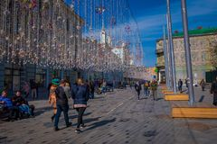 MOSKAU, RUSSLAND APRIL, 24, 2018: Leute in den festlichen Weihnachtslichtern auf Nikolskaya-Straße mit vielen Souvenirladen herei Stockfotografie