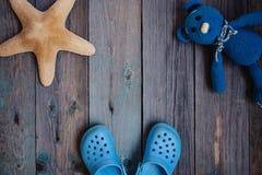 MOSKAU, RUSSLAND - 05 28 2018: Babystrand Pantoffel Starfish Teddybär betreffen Holztisch lizenzfreie stockbilder