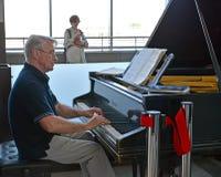 Moskau, Russland Der Mannespianist spielt auf Flügel im Warteraum der Yaroslavl-Station lizenzfreie stockfotografie