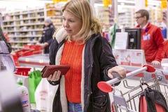 Moskau, Russland, 11/22/2018 Die junge Frau, die für Käufe an zahlt, checkout lizenzfreies stockfoto