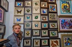 Moskau, Russland - 25. Februar 2017: Eine blonde Verkäuferin auf einem Standhintergrund mit getrockneten Insekten für Innenaussta Lizenzfreies Stockbild