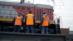 MOSKAU, RUSSLAND - FRÜHLING: Bahnarbeitskräfte sind, betrachtend stehend und einen überschreitenen Zug Beinnahaufnahme Arbeitskra stock video