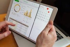 Moskau/Russland - 2. März 2013: In den Händen eines weißen iPad Pro auf dem Hintergrund von MacBook Zählung des Budgets stockfotos
