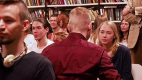 moskau RUSSLAND - März 2017 Leute sitzen im Reihenblick an ihren Partnern und an Lächeln circa im März 2017 in DOSTOEVSKI-BIBLIOT stock video