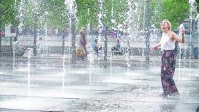 MOSKAU, RUSSLAND - MAI, 24, 2017 Junge Frau, die Haben des Spaßes im Parkbrunnen hat Heißer Sommer in der Stadt Stockbilder