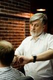 MOSKAU, RUSSLAND - 24. MAI 2018: Russischer Friseur Sergei Urazov tut Lizenzfreie Stockfotos