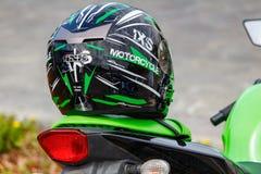 Moskau, Russland - 4. Mai 2019: Schwarzer Sportmotorradsturzhelm IXS mit grünen Streifen liegt auf einem grünen Ledersitz des Mot lizenzfreies stockfoto