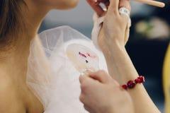 Moskau Russland - 11 13 2018: Nahaufnahme, die Lidschatten mit einer Bürste, die Hand des Maskenbildners mit Lippenstiftpalette a lizenzfreie stockfotos