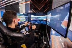 MOSKAU, RUSSLAND - 27. OKTOBER 2018 Junger Mann spielt auf einem Computer, der Simulator mit Großleinwänden läuft stockfoto