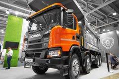 MOSKOU, 18 APRIL, 2018: Oranje grijze SCANIA-kippersvrachtwagen op Mijnbouwtentoonstelling De commerciële tentoongestelde voorwer royalty-vrije stock foto