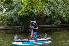 Moskou, de zomer 05 park-Juli, 2018: Jonge meisje en mens in strohoeden die zich op surfplanken bevinden stock foto