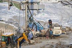MOSKOU, FEBRUARI 01, 2018: De wintermening over vuil zwaar bouwmateriaal, voertuigenarbeiders op het werk Het boren verrichtingen Stock Afbeeldingen